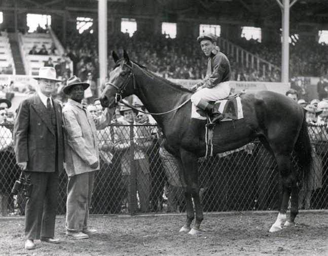 Twilight Tear (Conn McCreary up) in the winner's circle with trainer Ben Jones after winning the 1944 Rennert Handicap at Pimlico (The BloodHorse/Museum Collection)
