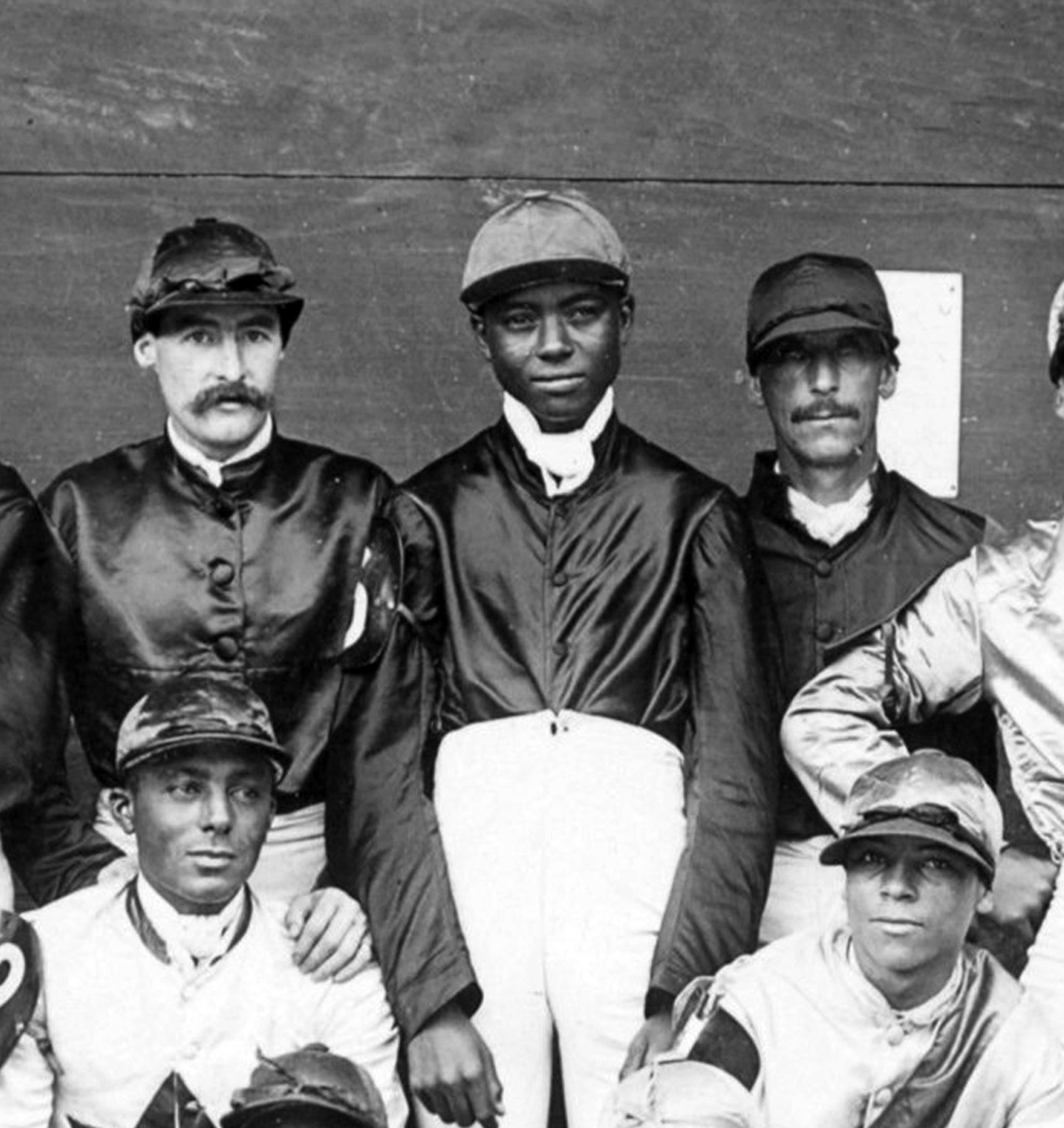"""Shelby """"Pike"""" Barnes (center) in a group portrait of a jockey colony (Keeneland Library Hemment Collection)"""