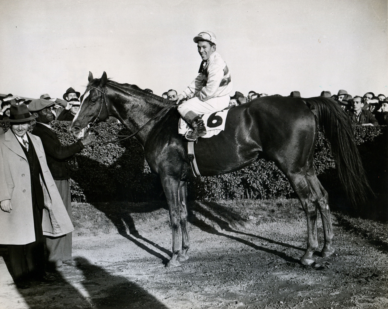 Conn McCreary and Stymie in the winner's circle with trainer Hirsch Jacobs after winning the 1947 Gallant Fox Handicap at Jamaica (Museum Collection)