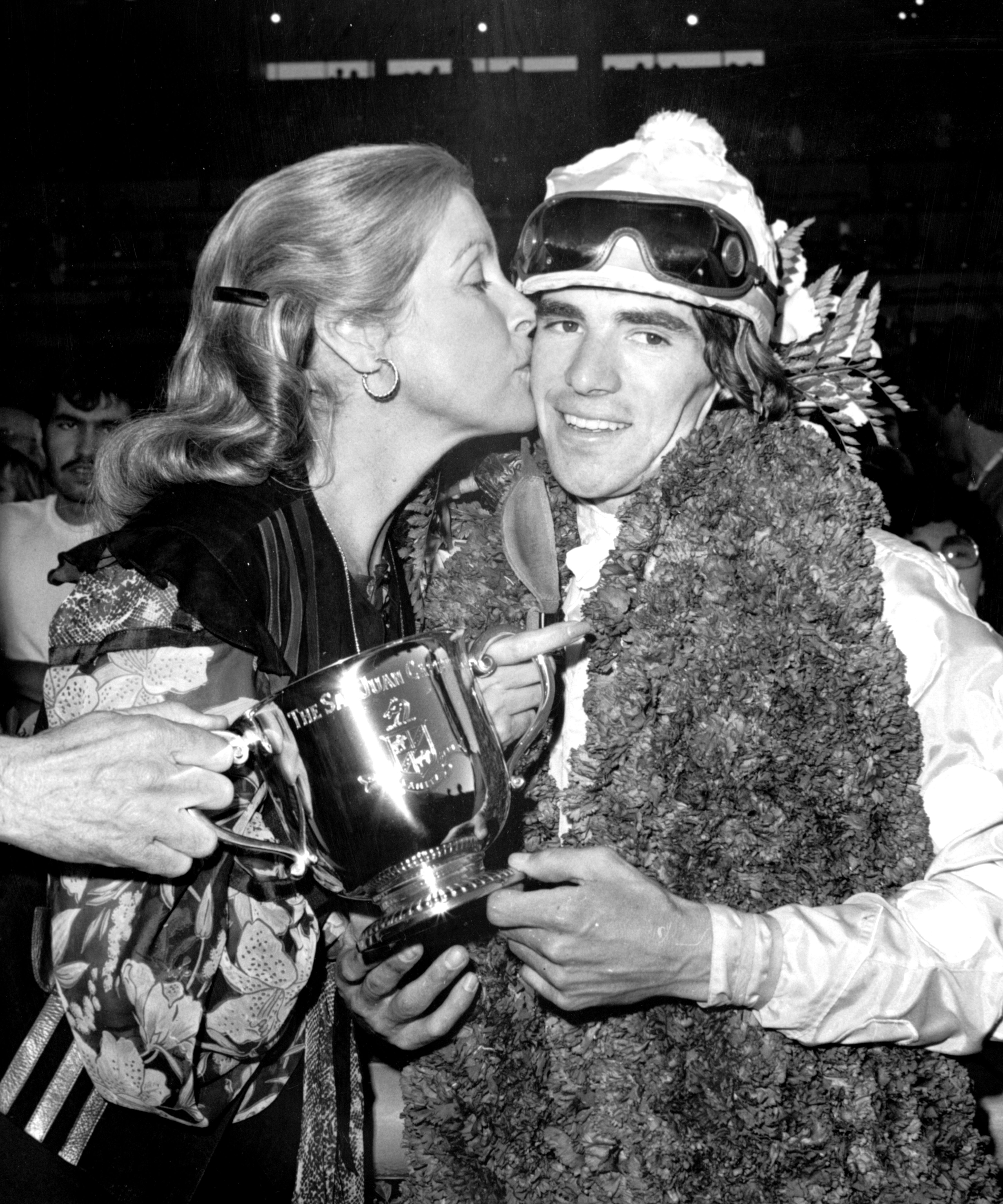 Darrel McHargue receives a kiss from Jacqueline Getty after winning the 1977 San Juan Capistrano Handicap (Keeneland Library Thoroughbred Times Collection)