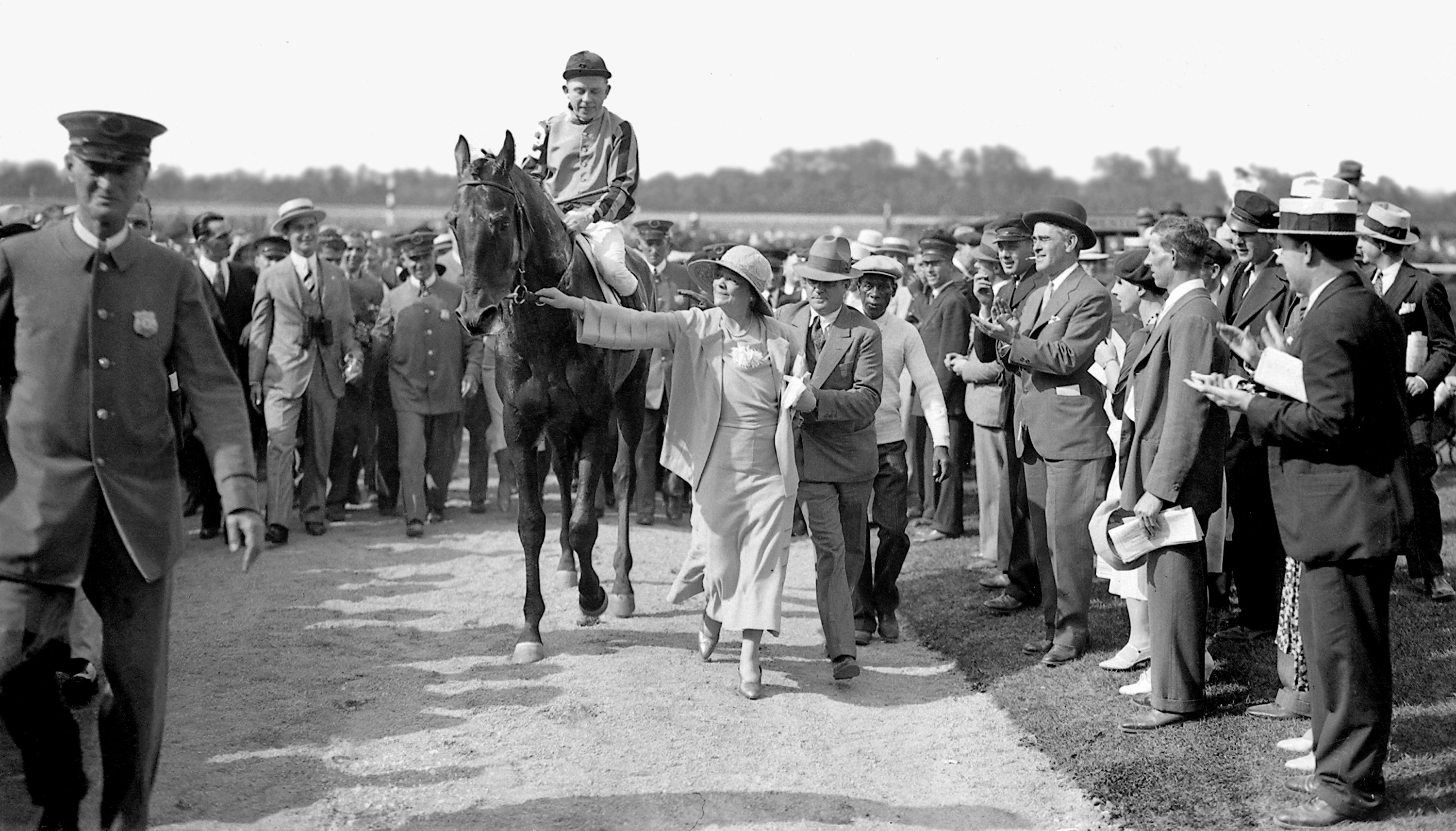 Helen Hay Whitney leading Twenty Grand, Charles Kurtsinger up, into the Belmont winner's circle (Keeneland Library Cook Collection)