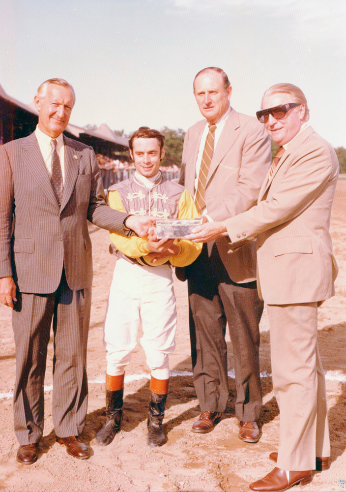 Paul Mellon, jockey Michael Venezia, and trainer MacKenzie Miller receive the trophy for the 1977 Jim Dandy (won by Music of Time) at Saratoga Race Course (Bert and Richard Morgan/Museum Collection)