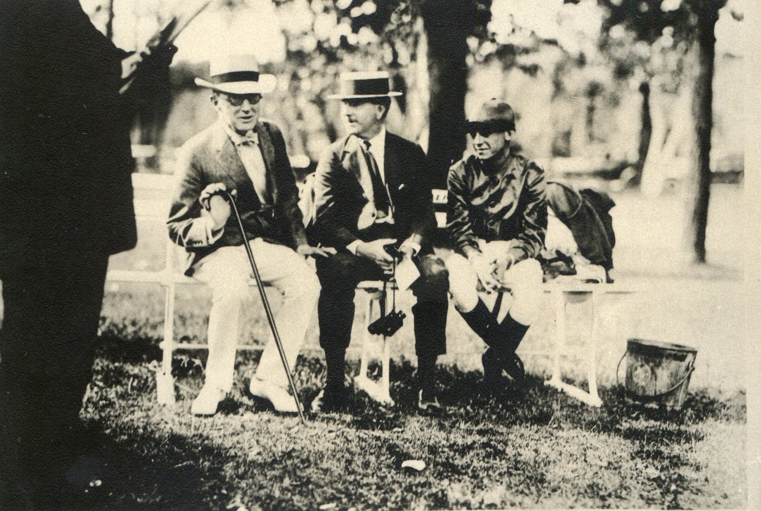 Trainer Tom Healey (center) and jockey Mack Garner share a bench with another unidentified man at Saratoga in 1920 (Museum Collection)