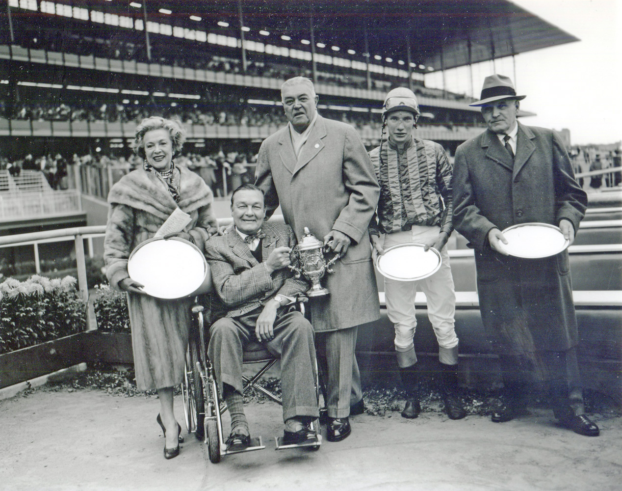 "Mr. and Mrs. Stephen ""Laddie"" Sanford, S. Bryce Wing, jockey Thomas Walsh, and trainer Hollie Hughes at the 1959 Grand National Steeplechase trophy presentation (won by Sun Dog) (Keeneland Library Morgan Collection/Museum Collection)"