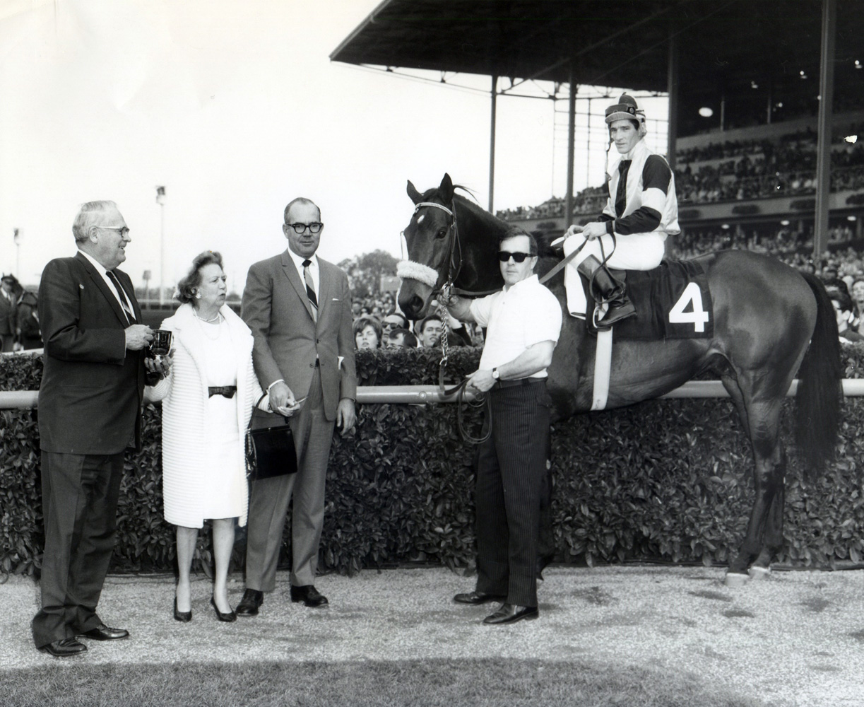 Owner Elizabeth Arden Graham and trainer Eddie Neloy join Gun Bow (Manuel Ycaza up) in the winner's circle for the 1965 San Antonio Handicap at Santa Anita (Santa Anita Photo/Museum Collection)