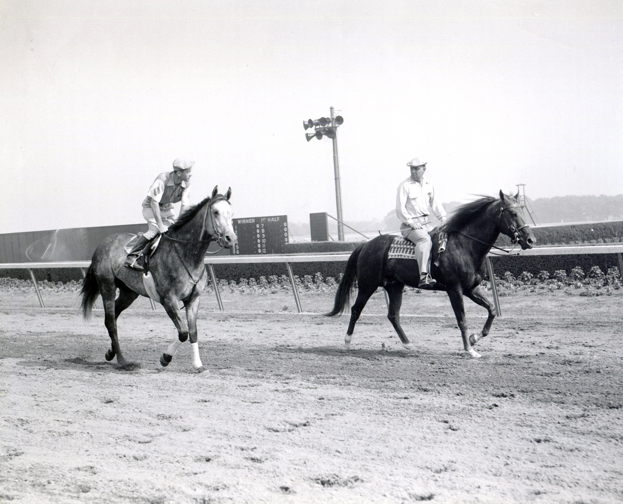 William C. Winfrey on a pony (on right) with Native Dancer and exercise rider B. Everson on the track (Museum Collection)